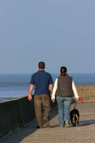 Walking The Dog. The rear view of a couple walking their dog on a promenade with the sea in the distance. (Sea out of focus Royalty Free Stock Image