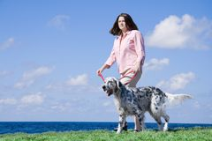 Walking the dog. Outdoors portrait of a girl walking her dog near the sea Stock Photography