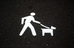 Walking the Dog. Walking, dog,exercise,leash, lead,sign, paint, road,bitumen,gravel,pavement,pet,offlead,onlead,offleash,offleash,symbol,directional,direction Royalty Free Stock Photography
