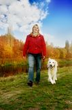Walking the dog. Woman walking with her golden retriever dog in autumn nature Stock Photo