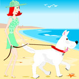 Walking the dog on the beach. A young lady is taking her dog for a walk on the beach Stock Photography