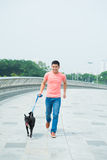 Walking with a dog. Image of a young man walking with his dog outside Stock Images