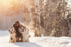 Walking with dog in winter. loving couple is walking in snow. Walking with dog in winter. Lover couple is walking in snow with dog. Sun light stock image
