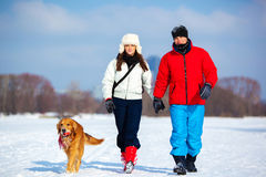 Walking with dog. Young couple walking with dog. Cold winter season and snowfield Stock Photos
