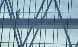 Walking down the glass path. Man walking down the glass construction of a futuristic building royalty free stock image