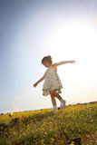 Walking down the hill. Little girl walking down a hill of yellow flowers Stock Photos