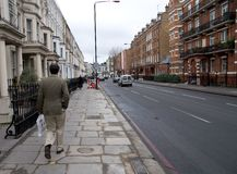 Walking down the road. Pedestrian walking down a London street in Earl's Court. It is a typical London street scene Royalty Free Stock Photography