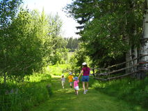 Walking down to the lake. Family visiting a farm in the summer royalty free stock photo