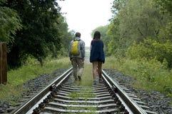 Walking down tracks. 2 people walking down train tracks stock photo