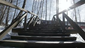 Walking down up on wooden stairs in forest park at winter, low POV view stock footage