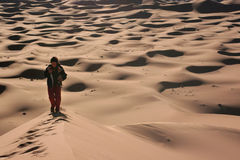 Walking on the dunes. Woman walking on the sand dunes (Morocco Royalty Free Stock Photography