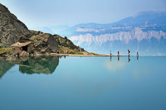 Walking the edge. Mountain climbers on the edge of a dammed mountain lake; taken from the lac du crozet, belledone mountains, france, in summer stock photos