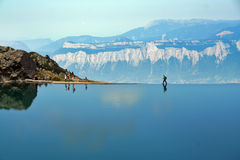 Walking the edge. Moutaineer walking along a dammed lake in the french alps stock images