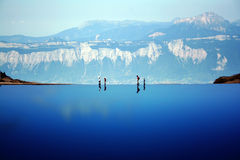 Walking the edge. Mountain climbers on the edge of a dammed mountain lake; taken from the lac du crozet, in the belledone mountains above grenoble, france, in royalty free stock images