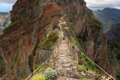 Walking on the edge of Madeira. Senior tourist in the mountains of Madeira at Pico do Areeiro Arieiro, while hiking to Pico Ruivo on a cloudy summer day with stock photo
