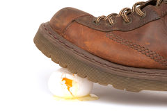 Walking On Egg Shel. Work boot walking on egg shells representing tension or making a big mess Stock Photos