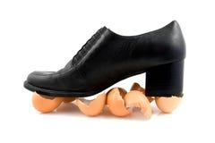 Walking on egg shells. Black shoe on egg shells; walking on eggs, isolated on white background royalty free stock photo