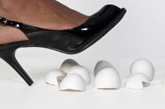 Walking on Eggshells. A woman in high heels walking on eggshells royalty free stock images