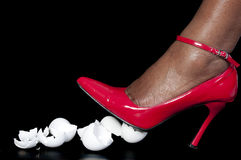 Walking on Eggshells. A woman in high heels walking on eggshells royalty free stock image