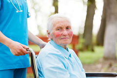 Walking with an Elderly Lady in Wheelchair Royalty Free Stock Image