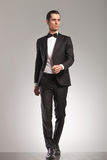 Walking elegant man in tuxedo is looking up to side stock photo