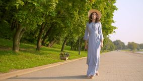 Walking on the embankment. Cinematic woman in a long blue retro dress and a straw hat walking on the embankment along the river. Slow Motion stock footage