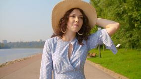 Walking on the embankment. Cinematic woman in a long blue retro dress and a straw hat walking on the embankment along the river. Slow Motion stock video