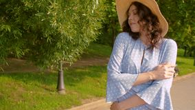 Walking on the embankment. Close up portrait of mysterious woman in a blue retro dress and a straw hat walking in the park. Slow Motion stock footage