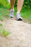 Walking exercise in summer. Woman walking on dirt footpath in forest Royalty Free Stock Photography