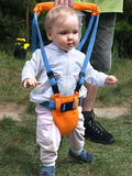 Walking exercises with Toddler Safety Harness. One year old baby learning to walk stock photo