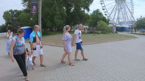 Walking families and individual. UKRAINE, BERDYANSK - Jule 19, 2019: Walking families and individual tourists along the city embankment of the main city beach stock footage