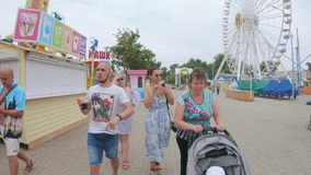 Walking families and individual. UKRAINE, BERDYANSK - Jule 19, 2019: Walking families and individual tourists along the city embankment of the main city beach stock video