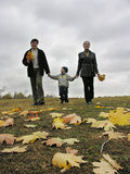 Walking family with autumn leaves and clouds. Walking family with autumn leaves closeup and clouds stock images
