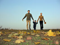 Walking family sundown autumn leaves. Walking family sundown. autumn leaves clouseup royalty free stock photo
