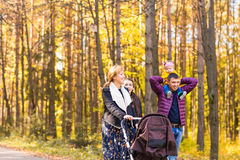 Walking family with two children in autumnal park.  Stock Images