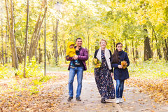 Walking family with two children in autumnal park.  Royalty Free Stock Image