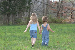 Walking on a farm. Young children holding hands and walking through a field Stock Photography