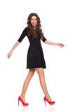 Walking Fashion Model in Black Mini Dress Stock Images