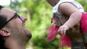 Dad throws a smiling daughter up. Walking father and daughter. Dad throws a smiling daughter up
