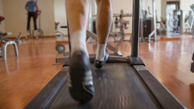 Walking feet on the treadmill. Middle shot of male feet walking on the treadmill in the fitness center stock footage