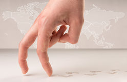 Walking fingers. Female fingers walking with footsteps behind them and a world map in the background Royalty Free Stock Image
