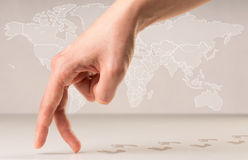 Walking fingers. Female fingers walking with footsteps behind them and a world map in the background Stock Photo