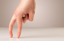 Walking fingers. Female fingers walking on white surface Royalty Free Stock Image
