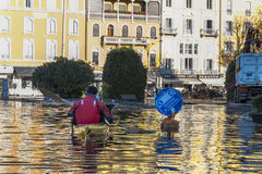 Canoing in the flood. 18/11/2014 Como ( Italy ) : a man going with the canoe in the streets of Como flooded by the heavy rainfalls of this autumn royalty free stock photos