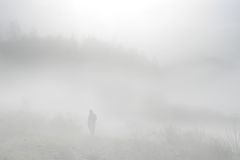 Walking in the fog. Senior taking a walk at the foggy lake Stock Photo