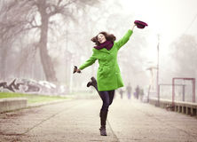 Walking in the Foggy Winter Day. Happy Young Woman Jumping with a Hat at the Footpath in the Foggy Spring Day Royalty Free Stock Image