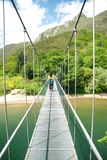 Walking on footbridge over river Stock Images