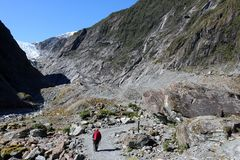 Walking footpath Franz Josef Glacier New Zealand. Lady with walking pole of footpath by the Waiho river leading up to the Franz Joseph Glacier Kā Roimata o Hine Stock Images