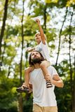Walking in the forest. Blond boy dressed in a white t-shirt sitting on the shoulders of his bearded father and keeps a stock image
