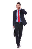 Walking forward while talking on the phone. Business man Walking forward and looking to a side while talking on the phone and carying a briefcase over white Stock Photo